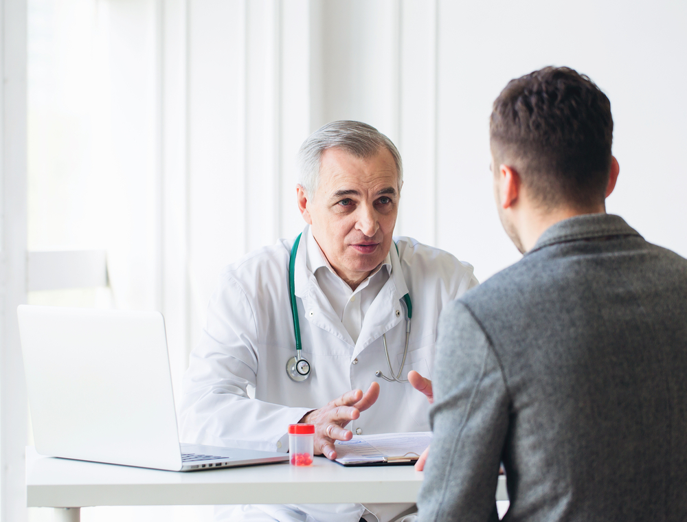A doctor at a low cost Los Angeles clinic discusses Kaposi's sarcoma with a patient.