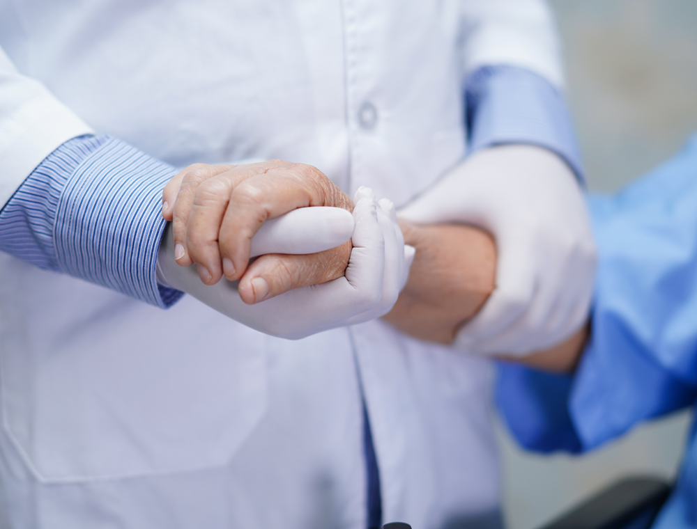 A doctor holding a patient's hand discussing Addison's disease.